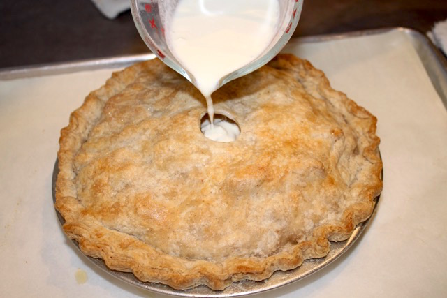 Pouring the heavy cream into the top of the almost baked Apple Cream Pie | urbnspice.com