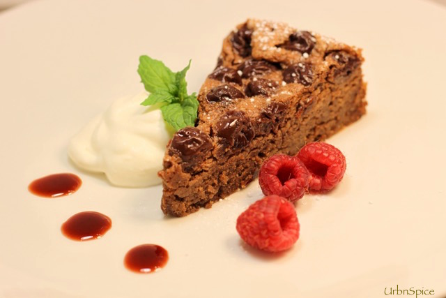 Chocolate Cherry Almond Torte plated with cherry syrup reduction and softly whipped cream | urbnspice.com