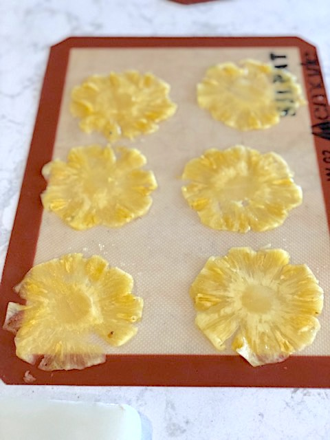 Pineapple garnish is made by drying paper thin slices of pineapple.